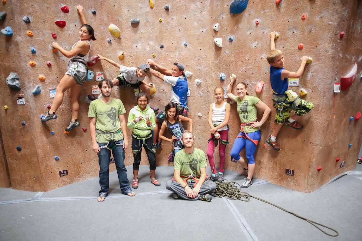 camp coaches and campers in front of climbing wall