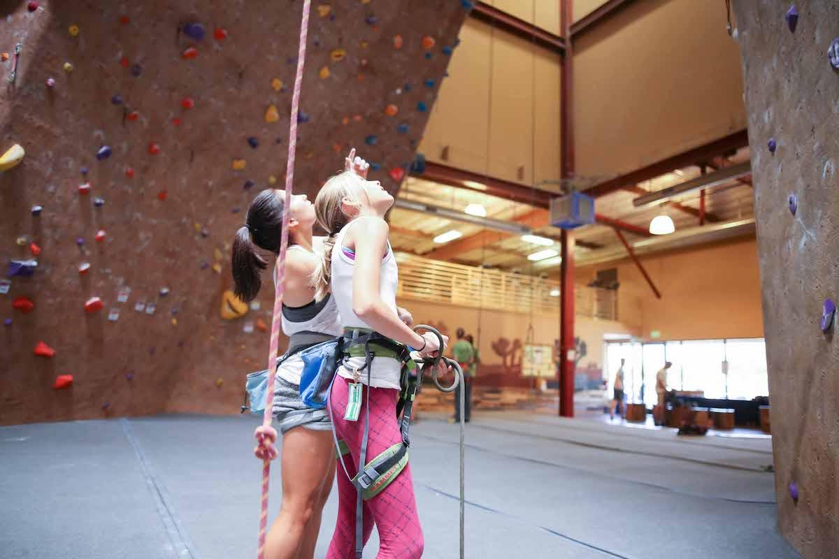 young girls looking up at climbing wall