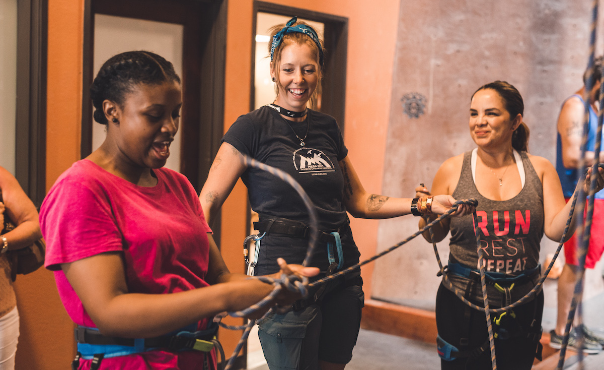Staff member leads a belay lesson for two participants
