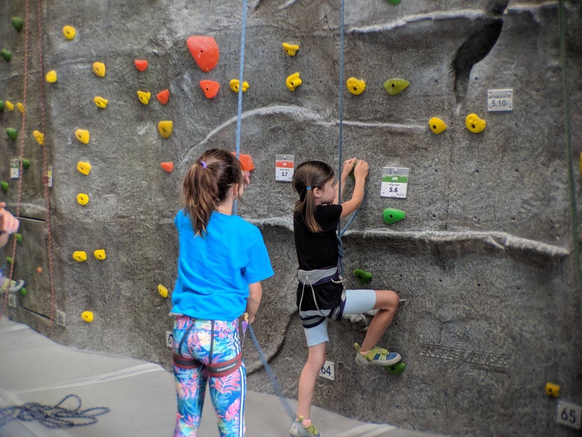 two young girls top rope climbing