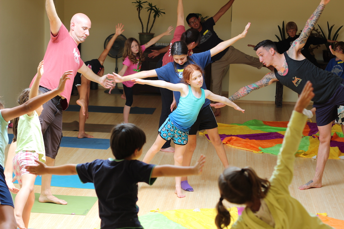 group of adults and children doing yoga