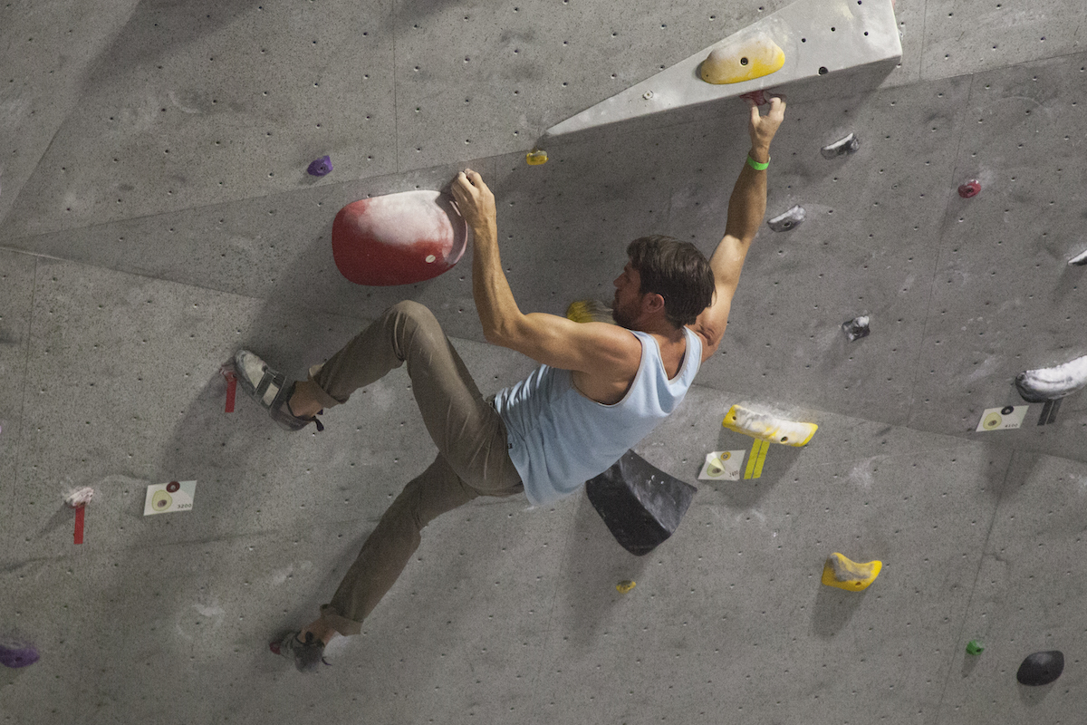 Two female climbers give each other a high five while a male climber looks on