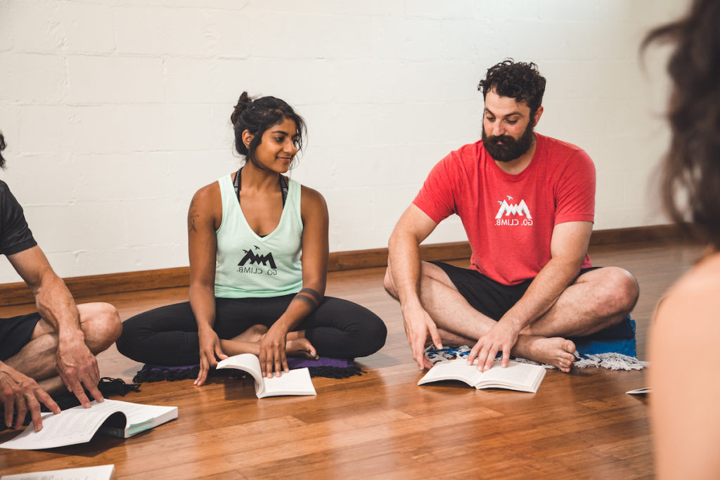 individuals reading a manual in a yoga teacher training class