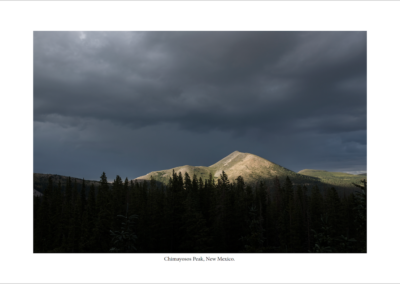 dark, cloud sky over mountains and trees