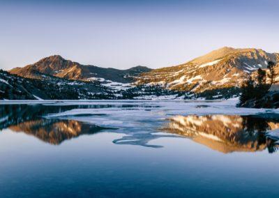 snowy mountains next to a lake