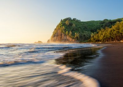 tropical beach next to a green hill