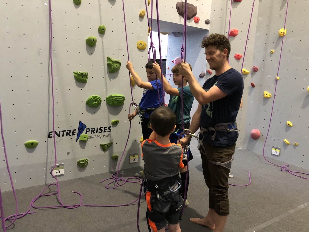 camp coach with three young climbers